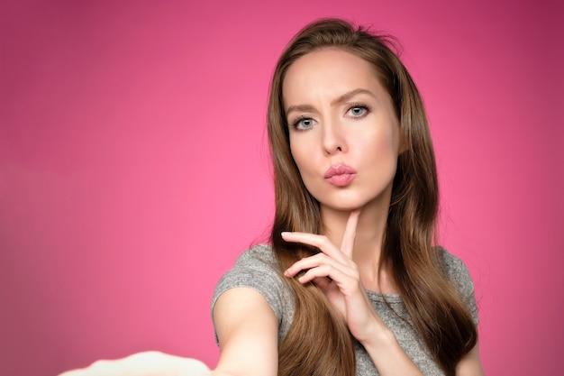 Mulher jovem e bonita europeia tomando selfie em fundo rosa