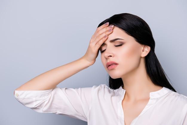 Mulher jovem e bonita exausta com excesso de trabalho em trajes formais com cabelos pretos tocando a cabeça, ela sofrendo de forte dor de cabeça