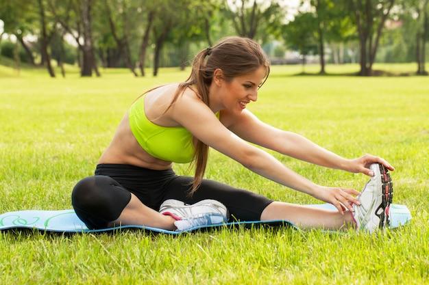 Mulher jovem e bonita exercitando em uma grama