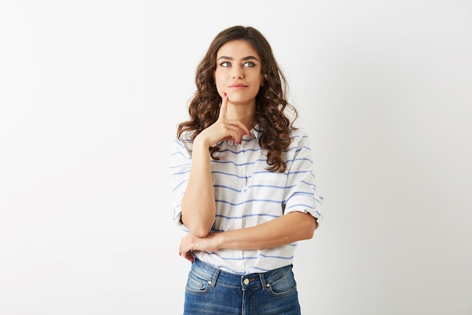 Mulher jovem e bonita, expressão facial concentrada, pensando no problema, estilo adolescente hippie, vestido de jeans, camisa, isolado no fundo branco, moda moderna, preocupado, ocupado