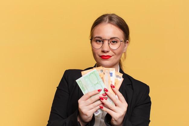 Mulher jovem e bonita. expressão feliz e surpresa. conceito de notas de euro