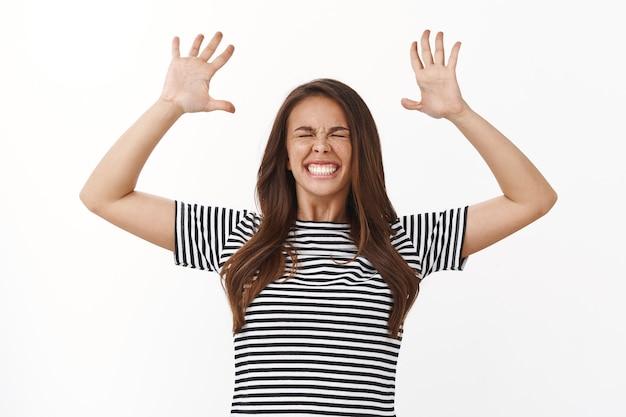 Mulher jovem e bonita extremamente feliz em uma camiseta listrada se sentindo como nas nuvens, pulando realizado e otimista, comemorando a vitória, levante as mãos, apertando os olhos e sorrindo despreocupado