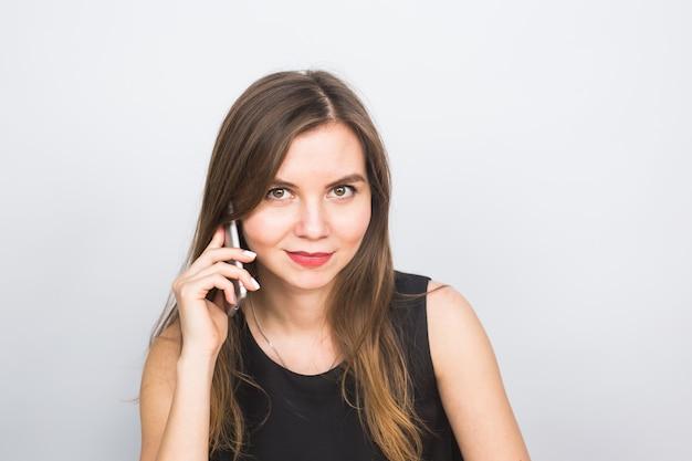 Mulher jovem e bonita fala falando por telefone celular, sobre um fundo branco.
