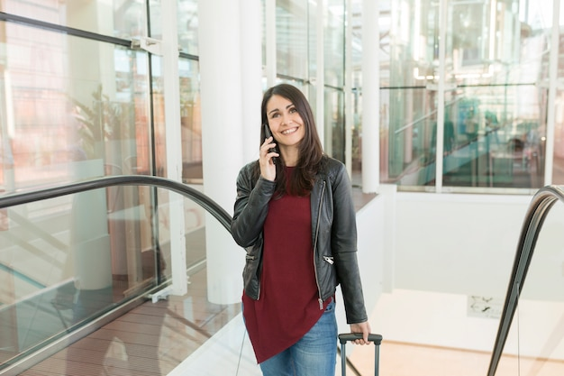 Mulher jovem e bonita falando em seu telefone móvel e sorrindo. conceito de viagens no aeroporto, ela está subindo escadas com um carrinho. diurno e estilo de vida