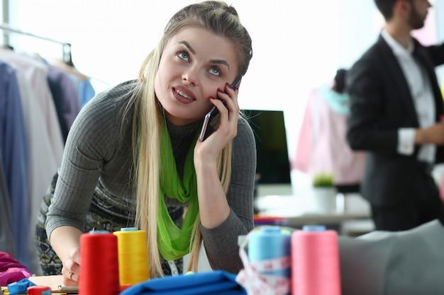 Mulher jovem e bonita falando no celular em alfaiataria