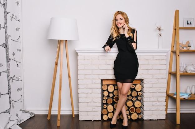 Mulher jovem e bonita falando por telefone e sorrindo na sala com interior moderno. ela é loira com cabelo ondulado. usando um vestido preto elegante. parede branca e lareira falsa.