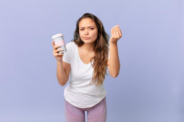 Mulher jovem e bonita fazendo capice ou gesto de dinheiro, dizendo para você pagar e segurando um café
