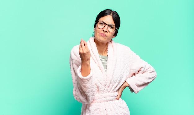 Mulher jovem e bonita fazendo capice ou gesto de dinheiro, dizendo para você pagar suas dívidas !. conceito de pijama