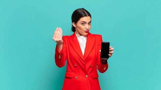 Mulher jovem e bonita fazendo capice ou gesto de dinheiro, dizendo para você pagar suas dívidas !. conceito de telefone inteligente