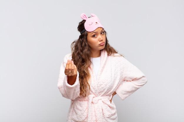 Mulher jovem e bonita fazendo capice ou gesto de dinheiro, dizendo para você pagar suas dívidas! vestindo pijama