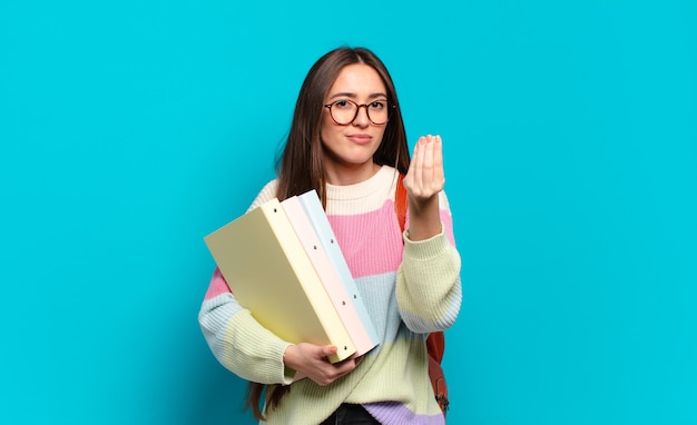 Mulher jovem e bonita fazendo capice ou gesto de dinheiro, dizendo para você pagar suas dívidas!