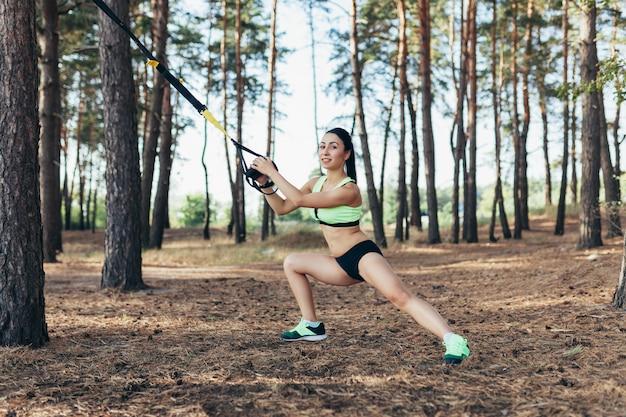 Mulher jovem e bonita fazendo exercício trx com estilingue de treinador de suspensão ao ar livre saudável