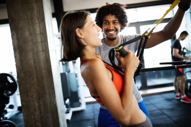 Mulher jovem e bonita fazendo exercícios com o personal trainer