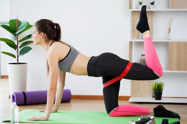 Mulher jovem e bonita fazendo exercícios de fitness em casa.