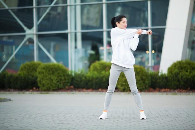 Mulher jovem e bonita fazendo exercícios no parque