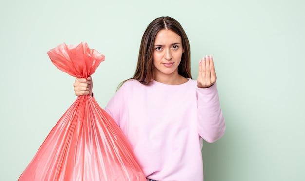 Mulher jovem e bonita fazendo gesto de capice ou dinheiro, dizendo para você pagar. conceito de lixo