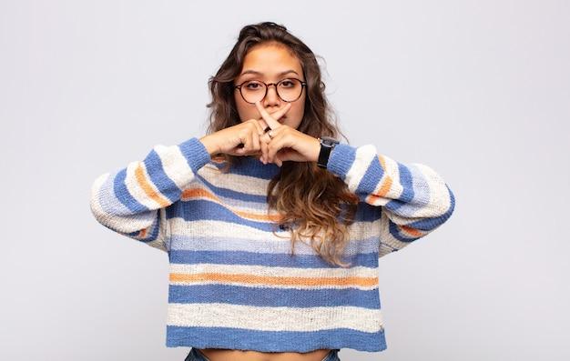 Mulher jovem e bonita fazendo gesto de censura, com os dedos cruzados sobre a boca