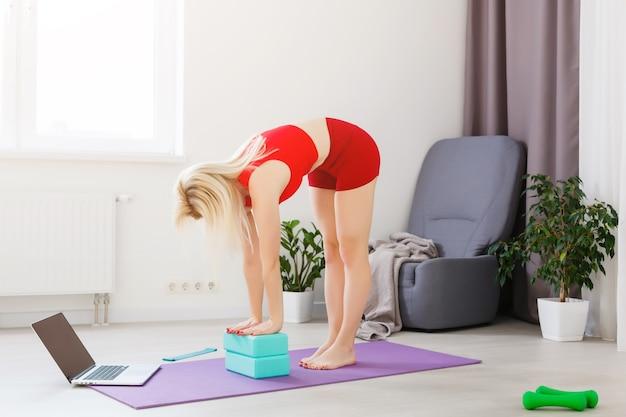 Mulher jovem e bonita fazendo ioga em casa.