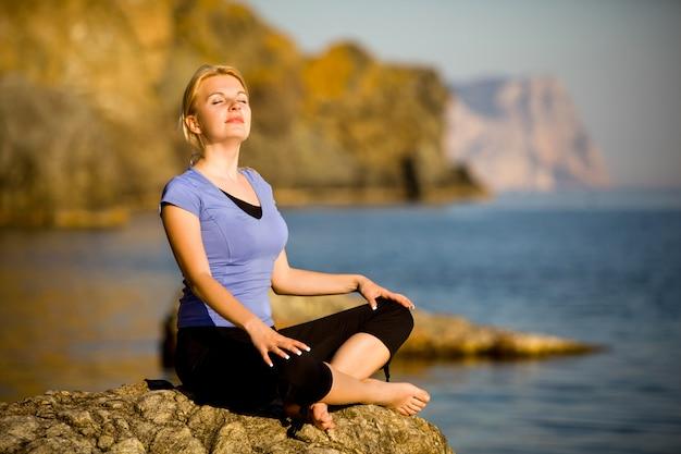 Mulher jovem e bonita fazendo ioga em uma pedra