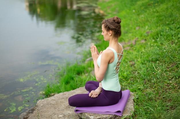 Mulher jovem e bonita fazendo ioga na natureza