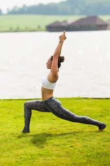 Mulher jovem e bonita fazendo ioga no parque matinal perto do lago