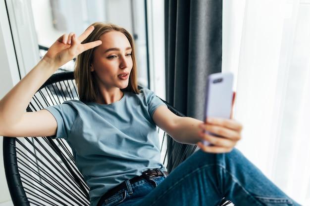 Mulher jovem e bonita fazendo selfie com seu telefone inteligente e sorrindo enquanto está sentada em uma cadeira grande em casa