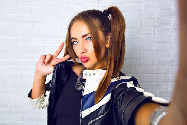 Mulher jovem e bonita fazendo selfie, maquiagem brilhante, linda caixa, dois rabos de cavalo fofos, jaqueta de couro de motociclista, parede urbana de grunge. divertindo-se sozinha, fazendo fotos para seus amigos.