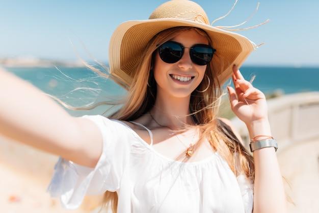 Mulher jovem e bonita fazendo selfie na praia no oceano