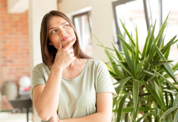 Mulher jovem e bonita fazendo um gesto em casa