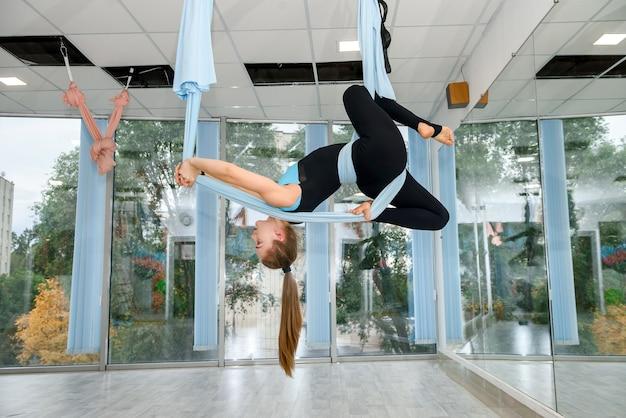 Mulher jovem e bonita fazendo voar ioga exercícios de alongamento no estúdio de fitness. estilo de vida saudável para todos