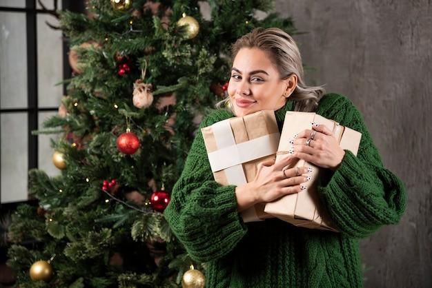 Mulher jovem e bonita feliz abraçando caixas de presente perto de uma árvore de natal