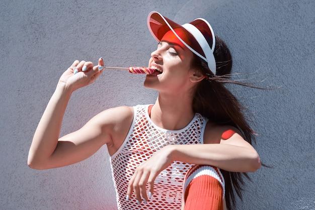Mulher jovem e bonita feliz andando em rolos, comendo doces, foto de verão