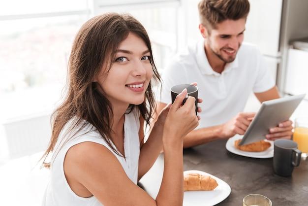 Mulher jovem e bonita feliz bebendo café enquanto o namorado dela está usando um tablet na cozinha