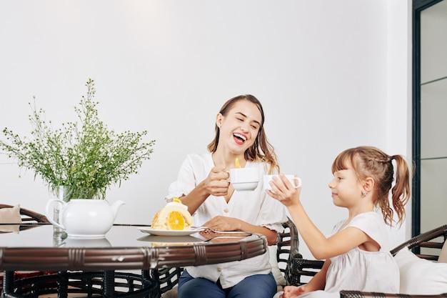 Mulher jovem e bonita feliz bebendo chá e comendo pãozinho de biscoito caseiro com a filha pequena