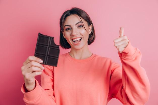 Mulher jovem e bonita feliz com barra de chocolate no fundo rosa e maquiagem brilhante