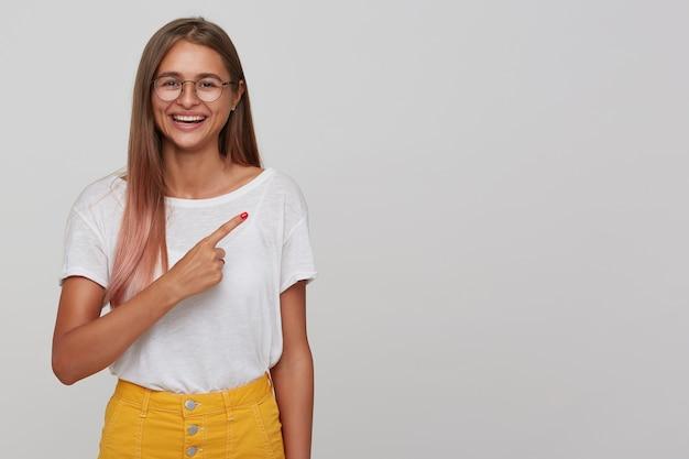Mulher jovem e bonita feliz com cabelo comprido castanho claro, usando óculos enquanto posava sobre uma parede branca, estando de bom humor e sorrindo alegremente com a mão levantada