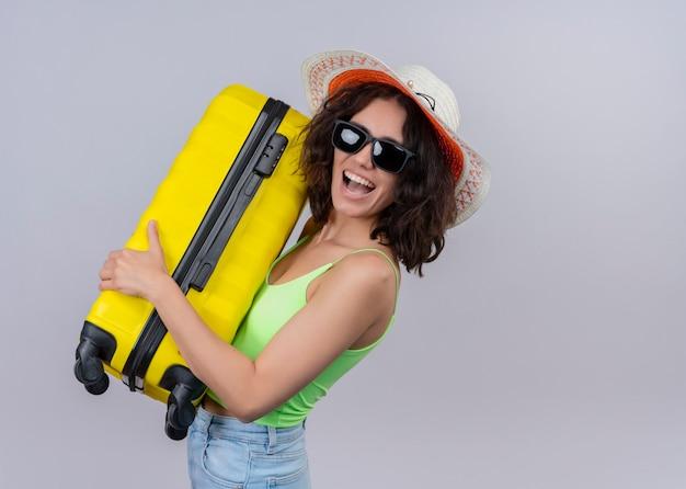 Mulher jovem e bonita feliz com chapéu e óculos escuros, segurando a mala na parede branca isolada com espaço de cópia