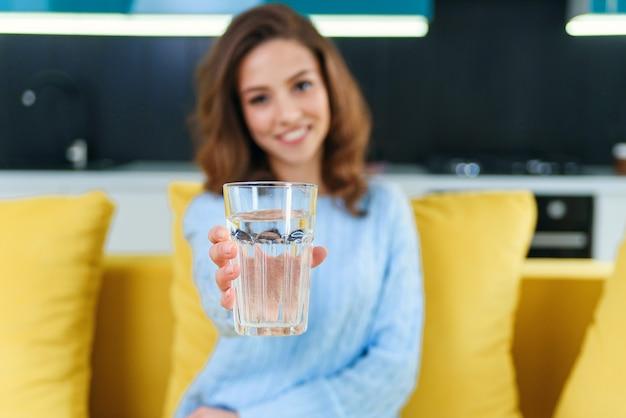 Mulher jovem e bonita feliz com copo de água cristalina, sentado no sofá amarelo macio.