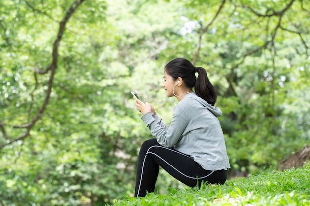 Mulher jovem e bonita feliz com fones de ouvido, ouvindo música e segurando o livro sentado na grama. retrato de garota verão