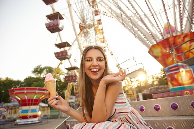 Mulher jovem e bonita feliz com longos cabelos castanhos posando sobre a roda gigante em um dia quente de verão, segurando a casquinha de sorvete e levantando a palma da mão, olhando com alegria