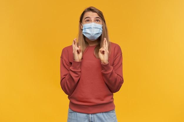Mulher jovem e bonita feliz com máscara protetora de vírus no rosto contra coronavírus mantém os dedos cruzados com as duas mãos, olhando para cima e fazendo um pedido sobre a parede amarela