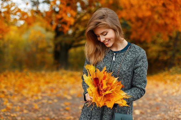 Mulher jovem e bonita feliz com roupas da moda de outono segurando folhas amarelas ao ar livre