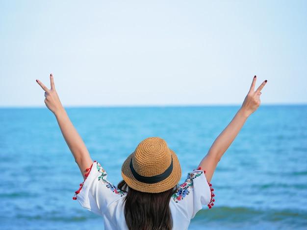Mulher jovem e bonita feliz com um chapéu, desfrutando de liberdade, relaxe e feliz na praia. conceito de viagens de verão.
