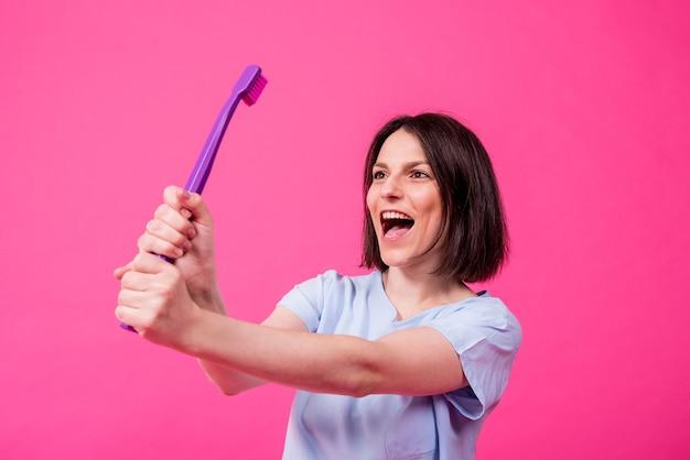 Mulher jovem e bonita feliz com uma escova de dentes grande em um fundo rosa em branco