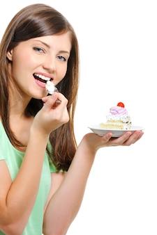 Mulher jovem e bonita feliz comendo bolo sobre fundo branco