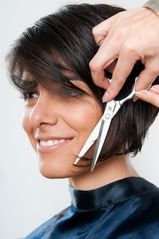 Mulher jovem e bonita feliz cortando cabelo no salão de cabeleireiro