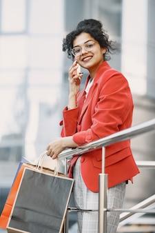 Mulher jovem e bonita feliz de óculos, com sacolas de compras, falando em um telefone celular de um shopping center