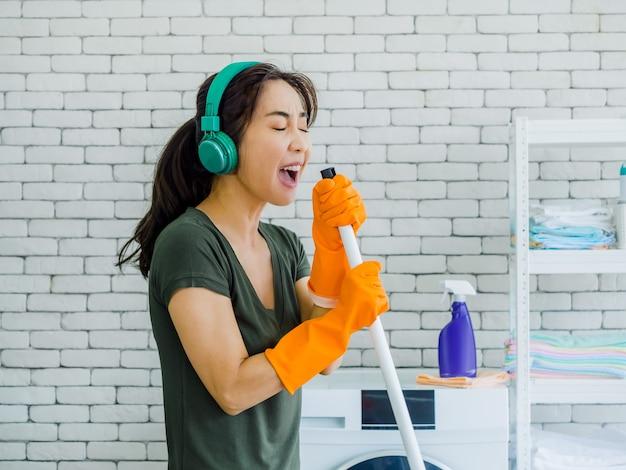 Mulher jovem e bonita feliz, dona de casa usando luvas de borracha laranja, ouvindo música com diversão cantando fone de ouvido verde com esfregão como um microfone na parede de tijolo branco em casa.