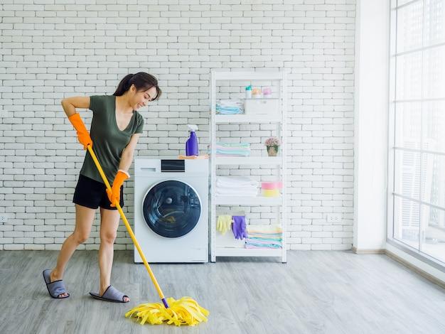 Mulher jovem e bonita feliz, dona de casa usando luvas de borracha protetoras laranja com rosto sorridente, limpando o chão com o esfregão perto da máquina de lavar na parede de tijolo branco perto da janela de vidro enorme.