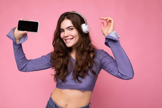 Mulher jovem e bonita, feliz e sorridente, vestindo roupa casual elegante, isolada na parede do fundo